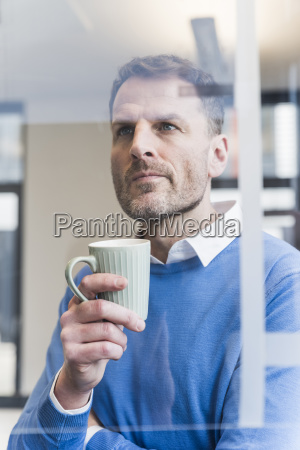 focused businessman holding cup of coffee