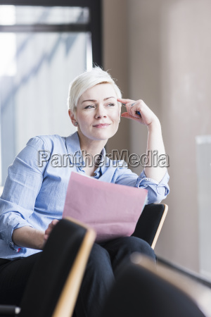 smiling woman in office holding document