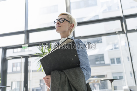 smiling woman in office building carrying