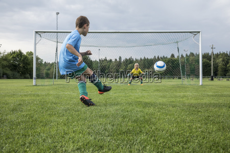 young football player kicking ball in