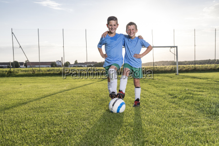 smiling young football players embracing on