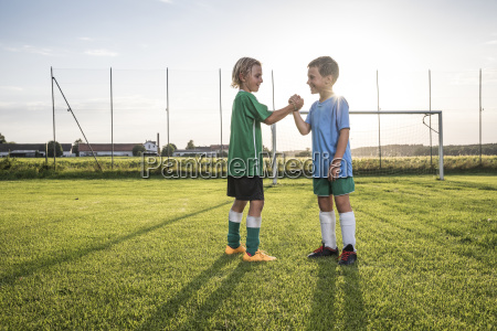 laechelnde junge fussballspieler schuetteln haende auf