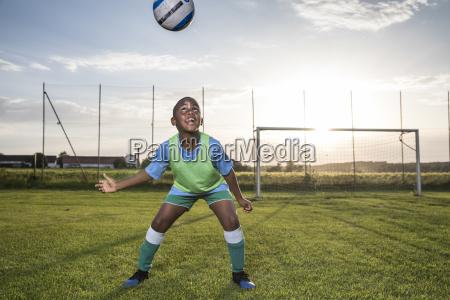 junger fussballspieler steuert den ball auf