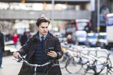 uk london businessman pushing bicycle
