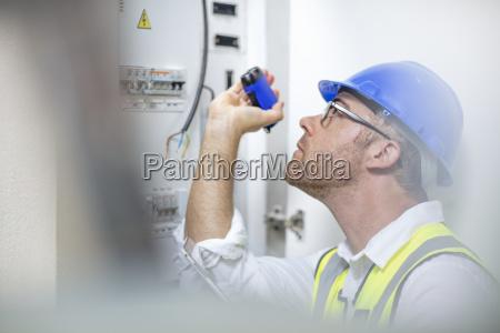 elektriker mit taschenlampe bei fusebox