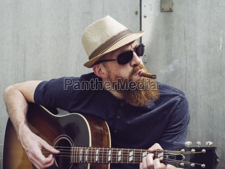 bearded man playing acoustic guitar and