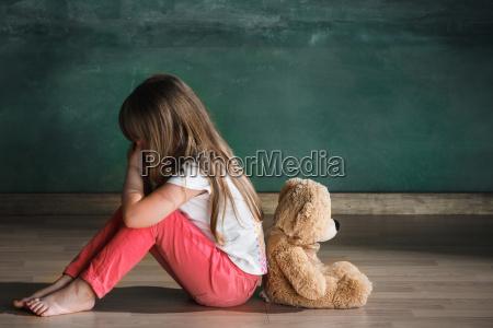 das kleine maedchen mit teddybaer sitzt