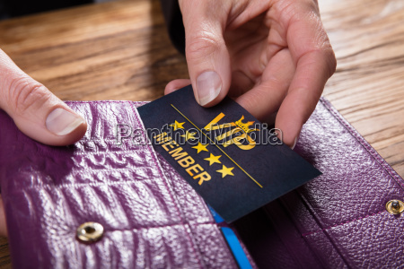 businessperson removing vip card from purse