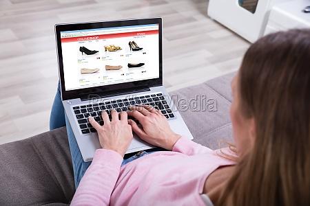 woman shopping footwears online on laptop