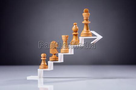 wooden chess piece on white arrow