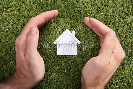menschliche hand schuetzt hausmodell