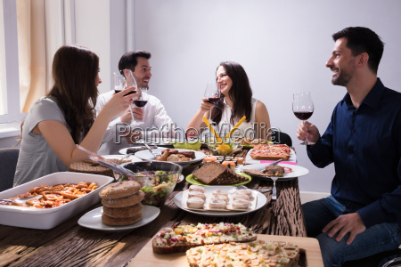 friends enjoying food with glass of