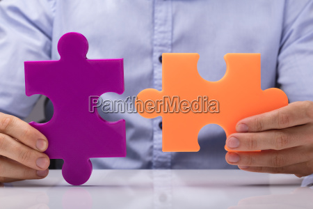 person holding two jigsaw puzzle