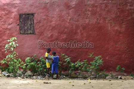 zwei kinder vor einer roten hausfassade