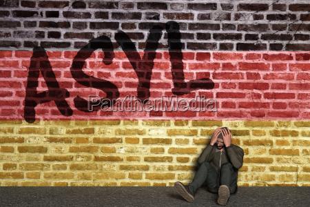 asylant sitzt vor mauer mit schriftzug
