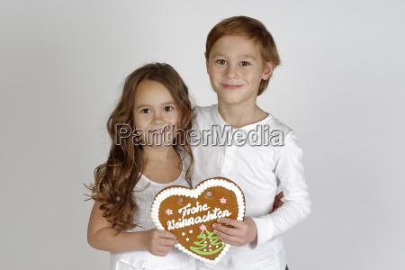 kinder mit einem lebkuchenherz frohe weihnachten