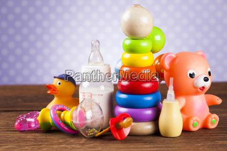 angefuellte babyspielwaren auf hoelzernem hintergrund