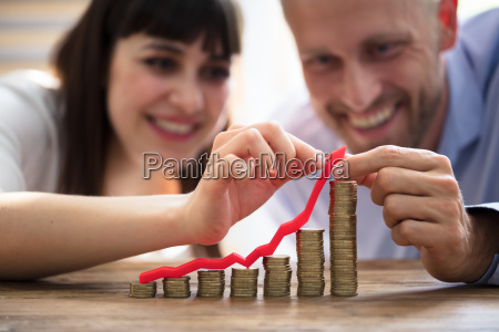 couple protecting increasing stacked coins