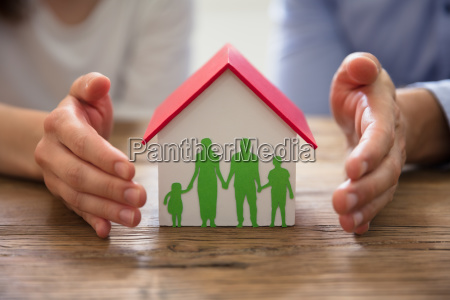 couple protecting family paper cut out