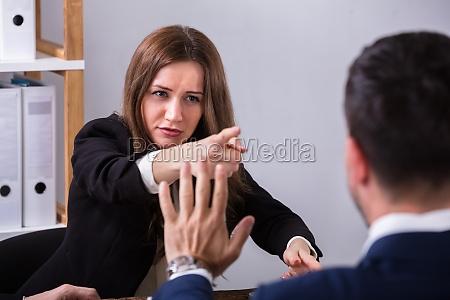 geschaeftsfrau die ihren kollegen schilt