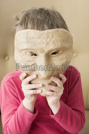 child holding mask in front of