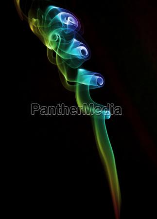 mehrfarbiger rauch vor schwarz