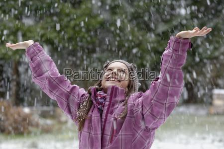maedchen freut sich ueber schneeflocken winter