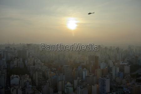 helikopter ueberfliegt eine grossstadtlandschaft mit hochhaeusern