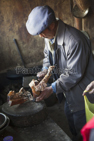 naxi chinese man chops dried meat