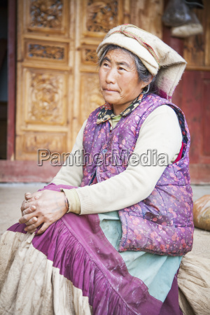 chinese naxi woman sits outside a