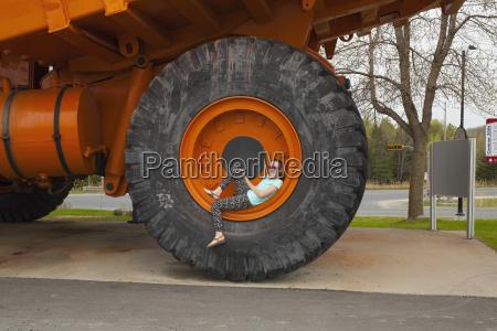 girl sitting inside wheel rim of