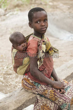young datoga girl carries baby brother
