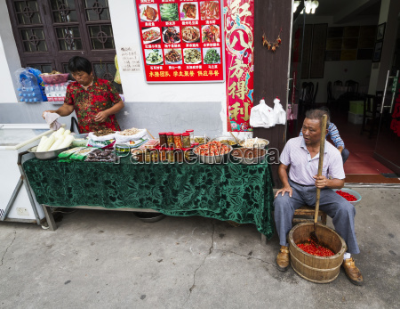 man crushing hot peppers hongcun anhui
