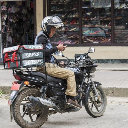 pizza lieferbote auf einem motorrad in
