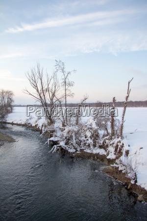 fluss am land teilweise mit schnee