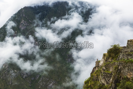 hiker atop waynu picchu reflects at