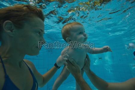 eltern die baby helfen zu schwimmen
