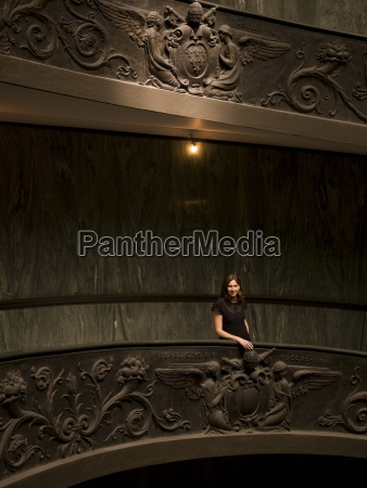 young woman standingon staircase in vatican