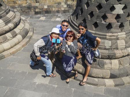 people amidst the latticed stone stupas