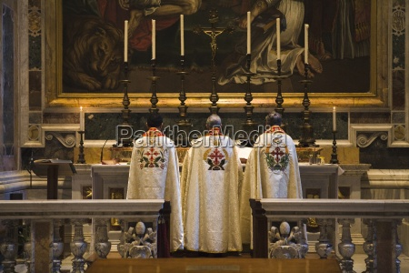 three priest standing at altar in