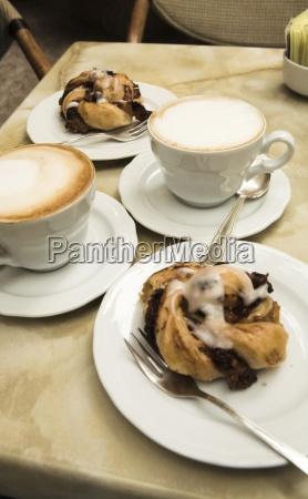 zwei cappucinos und dessert on table