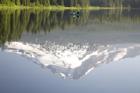 man on boat mt hood reflects