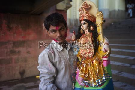 man bringing an idol to saraswati