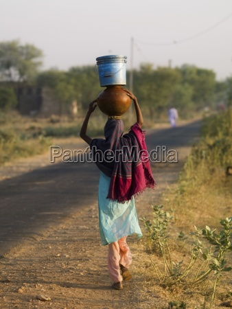 woman carrying bucket and bowl in