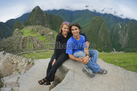 a young couple smiling at machu