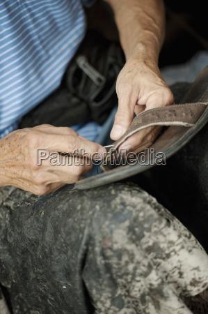a man fixing a shoe chiang