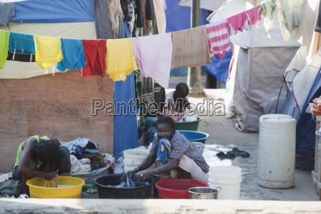 women wash clothes in large basins