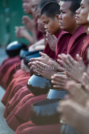 a row of buddhists chanting chiang