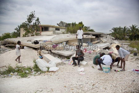 a family sits amidst the rubble