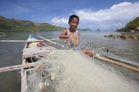 ein junger filipino junge entwirrt fischnetze